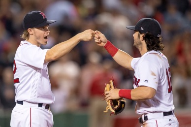 BOSTON, MA - AUGUST 5: Andrew Benintendi #16 and Brock Holt #12 of the Boston Red Sox celebrate a victory against the Chicago White Sox on August 5, 2017 at Fenway Park in Boston, Massachusetts. (Photo by Billie Weiss/Boston Red Sox/Getty Images) *** Local Caption *** Brock Holt; Andrew Benintendi
