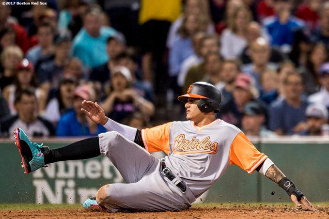 BOSTON, MA - AUGUST 25: Manny Machado #13 of the Baltimore Orioles slides into home as he scores during the fifth inning of a game against the Boston Red Sox on August 25, 2017 at Fenway Park in Boston, Massachusetts. (Photo by Billie Weiss/Boston Red Sox/Getty Images) *** Local Caption *** Manny Machado