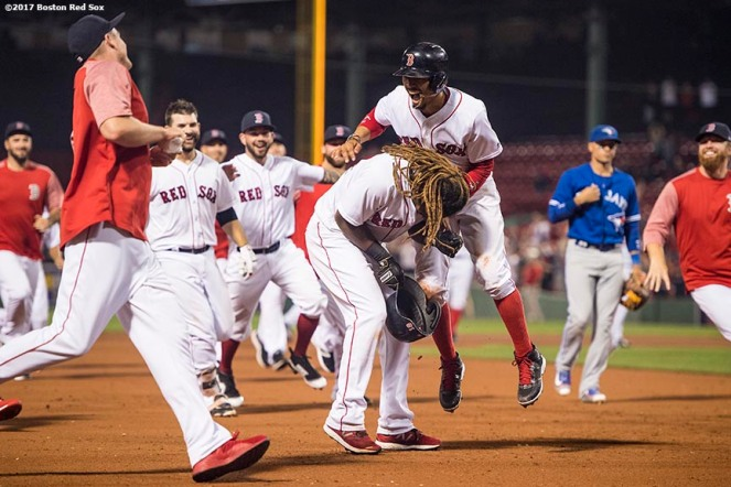 BOSTON, MA - SEPTEMBER 5: Hanley Ramirez #13 of the Boston Red Sox is mobbed by Mookie Betts #50 and teammates during the nineteenth inning of a game against the Toronto Blue Jays on September 5, 2017 at Fenway Park in Boston, Massachusetts. (Photo by Billie Weiss/Boston Red Sox/Getty Images) *** Local Caption *** Hanley Ramirez; Mookie Betts
