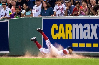BOSTON, MA - SEPTEMBER 13: Mookie Betts #50 of the Boston Red Sox dives into the outfield wall as he attempts to stop a ball from passing him during the first inning of a game against the Oakland Athletics on September 13, 2017 at Fenway Park in Boston, Massachusetts. (Photo by Billie Weiss/Boston Red Sox/Getty Images) *** Local Caption *** Mookie Betts