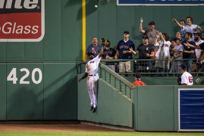 """Jackie Bradley Jr. #19 of the Boston Red Sox leaps over the wall to rob a home run ball hit by Aaron Judge #99 of the New York Yankees during the eighth inning of a game on July 16, 2017 at Fenway Park in Boston, Massachusetts."