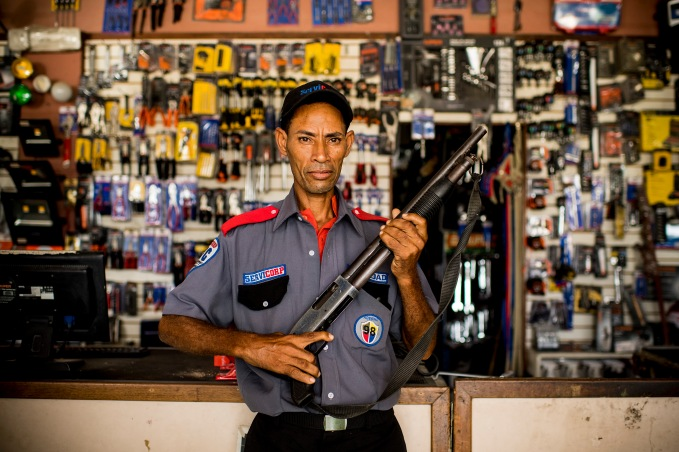 """A security guard poses for a portrait at the hardware store ferreteria in San Isidro during the 2017 Lindos Sueños trip in the Dominican Republic Thursday, July 20, 2017."""