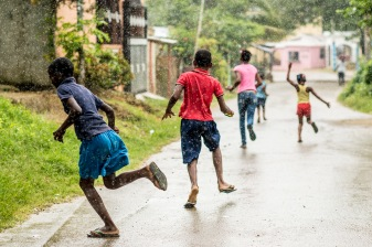 July 21, 2017, Boston, MA: Local kids run down the street in the rain in El Mamón during the 2017 Lindos Sueños trip in the Dominican Republic Friday, July 21, 2017. (Photo by Billie Weiss/Boston Red Sox)