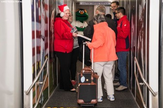 December 13, 2017, Boston, MA: Boston Red Sox employees give away tickets to passengers on a jetBlue flight at Logan Airport during The Gift Of Sox in Boston, Massachusetts Wednesday, December 13, 2017. (Photo by Billie Weiss/Boston Red Sox)