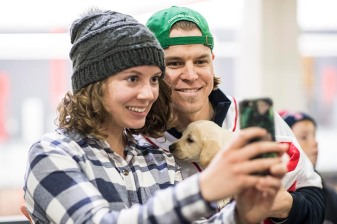 December 13, 2017, Roxbury, MA: Boston Red Sox infielder/outfielder Brock Holt poses for a selfie photograph with a student as he holds a puppy from the Great Dog Rescue of New England during a visit to Northeastern University duringThe Gift Of Sox in Boston, Massachusetts Wednesday, December 13, 2017. (Photo by Billie Weiss/Boston Red Sox)