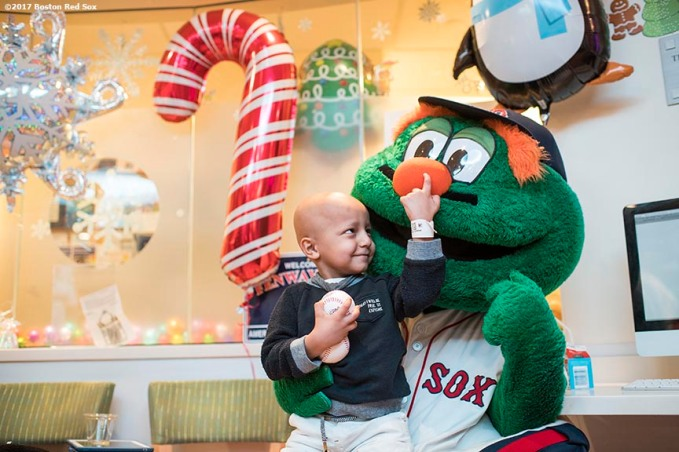 December 14, 2017, Boston, MA: A patient plays with Boston Red Sox mascot Wally the Green Monster during a visit to The Jimmy Fund at Dana-Farber Cancer Institute as part of the 2017 Holiday Caravan in Boston, Massachusetts Thursday, December 14, 2017. (Photo by Billie Weiss/Boston Red Sox)
