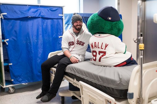 December 15, 2017, Boston, MA: Boston Red Sox pitcher Austin Maddox reacts with mascot Wally during a visit to Massachusetts General Hospital as part of the 2017 Red Sox Holiday Caravan in Boston, Massachusetts Friday, December 15, 2017. (Photo by Billie Weiss/Boston Red Sox)