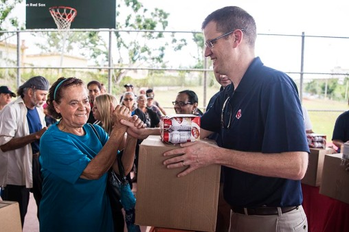 SAN JUAN, PUERTO RICO - JANUARY 30: Boston Red Sox President and CEO Sam Kennedy distributes food to residents during a Boston Red Sox hurricane relief trip from Boston, Massachusetts to Caguas, Puerto Rico on January 30, 2018 . (Photo by Billie Weiss/Boston Red Sox/Getty Images) *** Local Caption *** Sam Kennedy