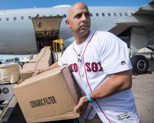SAN JUAN, PUERTO RICO - JANUARY 30: Manager Alex Cora of the Boston Red Sox helps unload boxes off of the plane during a Boston Red Sox hurricane relief trip from Boston, Massachusetts to Caguas, Puerto Rico on January 30, 2018 . (Photo by Billie Weiss/Boston Red Sox/Getty Images) *** Local Caption *** Alex Cora