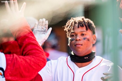 BOSTON, MA - APRIL 7: Rafael Devers #11 of the Boston Red Sox high fives teammates after hitting a solo home run during the seventh inning of a game against the Tampa Bay Rays on April 7, 2018 at Fenway Park in Boston, Massachusetts. (Photo by Billie Weiss/Boston Red Sox/Getty Images) *** Local Caption *** Rafael Devers