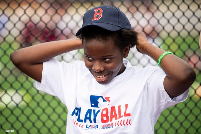 SPRINGFIELD, MA. - APRIL 27: A participant puts on a Boston Red Sox hat during a Major League Baseball Play Ball event on Friday, April 27, 2018 at Berry-Allen Field at Springfield College in Springfield, Massachusetts. (Photo by Billie Weiss/MLB Photos via Getty Images) *** Local Caption ***