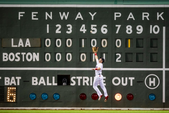 BOSTON, MA - JUNE 28: Andrew Benintendi #16 of the Boston Red Sox leaps as he catches a line drive in front of the Green Monster scoreboard during the eighth inning of a game against the Los Angeles Angels of Anaheim on June 28, 2018 at Fenway Park in Boston, Massachusetts. (Photo by Billie Weiss/Boston Red Sox/Getty Images) *** Local Caption *** Andrew Benintendi
