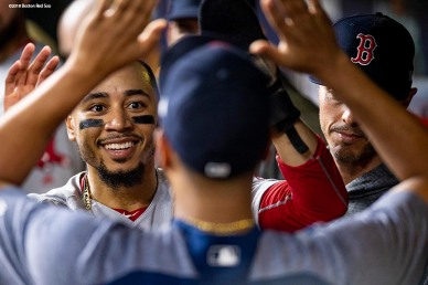 HOUSTON, TX - OCTOBER 17: Mookie Betts #50 of the Boston Red Sox reacts as he high fives teammates after scoring during the eighth inning of game four of the American League Championship Series against the Houston Astros on October 17, 2018 at Minute Maid Park in Houston, Texas. (Photo by Billie Weiss/Boston Red Sox/Getty Images) *** Local Caption *** Mookie Betts