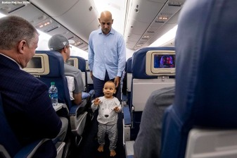 HOUSTON, TX - OCTOBER 18: Manager Alex Cora of the Boston Red Sox walks down the aisle on the plane with his son after clinching the American League Championship Series in game five against the Houston Astros on October 18, 2018 at Minute Maid Park in Houston, Texas. (Photo by Billie Weiss/Boston Red Sox/Getty Images) *** Local Caption ***Alex Cora