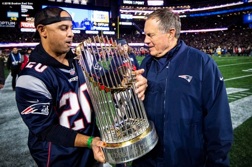 FOXBOROUGH, MA - NOVEMBER 4: Manager Alex Cora of the Boston Red Sox hands the World Series trophy to head coach Bill Belichick of the New England Patriots before a game against the Green Bay Packers on November 4, 2018 at Gillette Stadium in Foxborough, Massachusetts. (Photo by Billie Weiss/Boston Red Sox/Getty Images) *** Local Caption *** Alex Cora; Bill Belichick