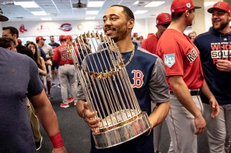 FT. MYERS, FL - FEBRUARY 18: Mookie Betts #50 of the Boston Red Sox holds the 2018 World Series trophy during a team meeting before a team workout on February 18, 2019 at JetBlue Park at Fenway South in Fort Myers, Florida. (Photo by Billie Weiss/Boston Red Sox/Getty Images) *** Local Caption *** Mookie Betts