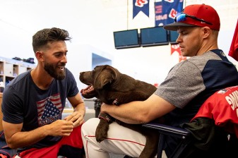 FT. MYERS, FL - FEBRUARY 28: Rick Porcello #22 and Brock Holt #12 of the Boston Red Sox play with a dog before a game against the Washington Nationals on February 28, 2019 at JetBlue Park at Fenway South in Fort Myers, Florida. (Photo by Billie Weiss/Boston Red Sox/Getty Images) *** Local Caption *** Brock Holt