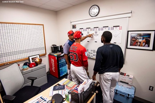 FT. MYERS, FL - FEBRUARY 28: Manager Alex Cora of the Boston Red Sox works in his office with Mookie Betts #50 and Jackie Bradley Jr. #19 before a game against the Washington Nationals on February 28, 2019 at JetBlue Park at Fenway South in Fort Myers, Florida. (Photo by Billie Weiss/Boston Red Sox/Getty Images) *** Local Caption *** Alex Cora; Mookie Betts