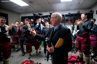 March 22, 2019, Boston, MA: Head coach Jerry York of Boston College is presented with the game puck by teammates in the locker room after defeating University of Massachusetts in the 2019 Hockey East semi-final game to record his 600th career win at TD Garden in Boston, Massachusetts Friday, March 22, 2019. (Photo by Billie Weiss/Boston College)