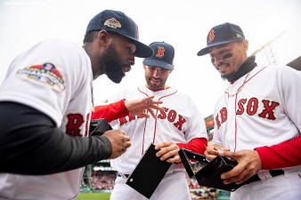 BOSTON, MA - APRIL 9: Jackie Bradley Jr. #19, J.D. Martinez #28, and Mookie Betts #50 of the Boston Red Sox look at their rings during a 2018 World Series championship ring ceremony before the Opening Day game against the Toronto Blue Jays on April 9, 2019 at Fenway Park in Boston, Massachusetts. (Photo by Billie Weiss/Boston Red Sox/Getty Images) *** Local Caption *** Jackie Bradley Jr.; J.D. Martinez; Mookie Betts