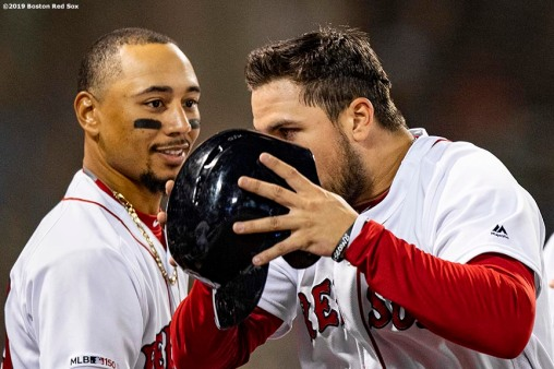 BOSTON, MA - APRIL 30: Michael Chavis #23 of the Boston Red Sox has his helmet removed by Mookie Betts #50 after scoring during the fourth inning of a game against the Oakland Athletics on April 30, 2019 at Fenway Park in Boston, Massachusetts. (Photo by Billie Weiss/Boston Red Sox/Getty Images) *** Local Caption *** Michael Chavis; Mookie Betts
