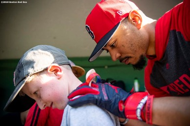 BOSTON, MA - MAY 18: Mookie Betts #50 of the Boston Red Sox signs autographs for a Jimmy Fund patient before a game against the Houston Astros on May 18, 2019 at Fenway Park in Boston, Massachusetts. (Photo by Billie Weiss/Boston Red Sox/Getty Images) *** Local Caption *** Mookie Betts