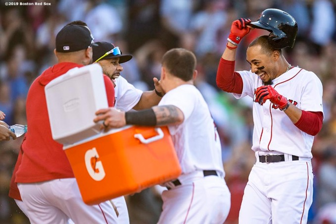 BOSTON, MA - JUNE 12: Mookie Betts #50 of the Boston Red Sox reacts with teammates after being walked to force in the game winning run on a walk off during the ninth inning of a game against the Texas Rangers on June 12, 2019 at Fenway Park in Boston, Massachusetts. (Photo by Billie Weiss/Boston Red Sox/Getty Images) *** Local Caption *** Mookie Betts
