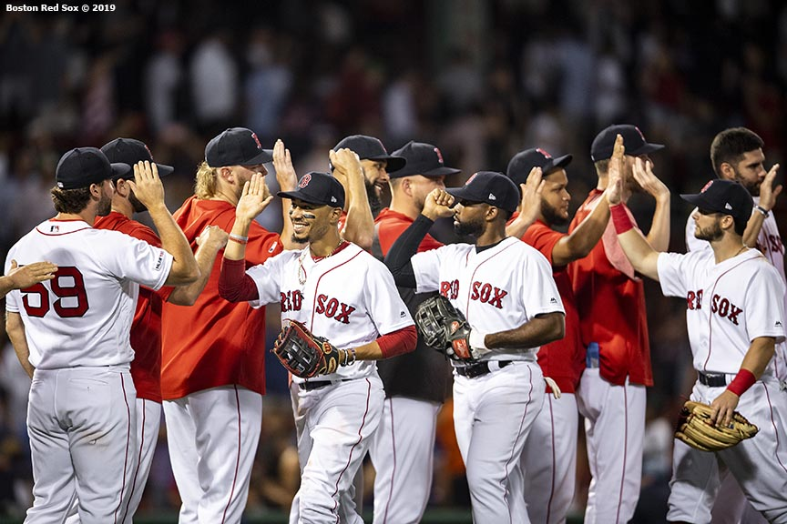 BOSTON, MA - JULY 15: Mookie Betts #50, Jackie Bradley Jr. #19, and Andrew Benintendi #16 of the Boston Red Sox high five teammates following a victory against the Toronto Blue Jays on July 15, 2019 at Fenway Park in Boston, Massachusetts. (Photo by Billie Weiss/Boston Red Sox/Getty Images) *** Local Caption *** Mookie Betts; Jackie Bradley Jr.; Andrew Benintendi