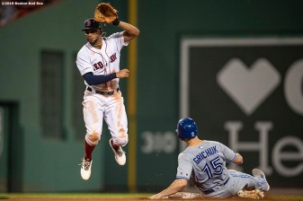 BOSTON, MA - JULY 17: Xander Bogaerts #2 of the Boston Red Sox turns a double play over Randal Grichuck #15 of the Toronto Blue Jays during the fourth inning of a game on July 17, 2019 at Fenway Park in Boston, Massachusetts. (Photo by Billie Weiss/Boston Red Sox/Getty Images) *** Local Caption *** Xander Bogaerts; Randal Grichuck