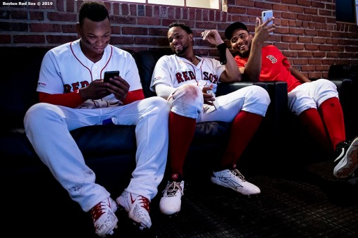 BOSTON, MA - AUGUST 7: Rafael Devers #11, Xander Bogaerts #2, and Darwinzon Hernandez #63 of the Boston Red Sox react as they use their phones during a rain delay during a game against the Kansas City Royals on August 7, 2019 at Fenway Park in Boston, Massachusetts. (Photo by Billie Weiss/Boston Red Sox/Getty Images) *** Local Caption *** Rafael Devers; Xander Bogaerts; Darwinzon Hernandez