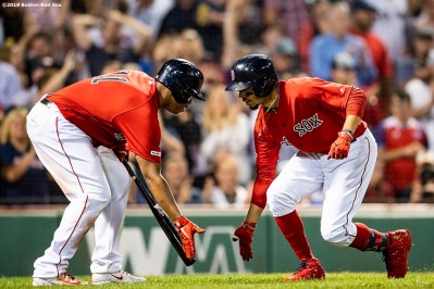 BOSTON, MA - AUGUST 16: Mookie Betts #50 of the Boston Red Sox high fives Rafael Devers #11 after hitting a solo home run during the eighth inning of a game against the Baltimore Orioles on August 16, 2019 at Fenway Park in Boston, Massachusetts. (Photo by Billie Weiss/Boston Red Sox/Getty Images) *** Local Caption *** Mookie Betts; Rafael Devers