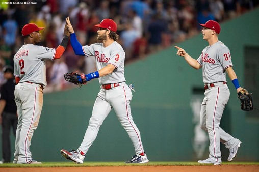 BOSTON, MA - AUGUST 20: Jean Segura #2, Bryce Harper #3, and Corey Dickerson #31 of the Philadelphia Phillies celebrate a victory against the Boston Red Sox on August 20, 2019 at Fenway Park in Boston, Massachusetts. (Photo by Billie Weiss/Boston Red Sox/Getty Images) *** Local Caption *** Jean Segura; Bryce Harper; Corey Dickerson