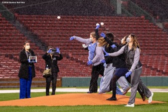 BOSTON, MA - APRIL 9: Medical professionals from Beth Israel Deaconess Medical Center throw out a ceremonial first pitch as they are welcomed onto the empty field at Fenway Park in recognition of their work during the coronavirus pandemic on April 9, 2020 at Fenway Park in Boston, Massachusetts. The welcoming was filmed for the 'Some Good News With John Krasinski' YouTube series. (Photo by Billie Weiss/Boston Red Sox/Getty Images) *** Local Caption ***
