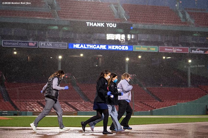 BOSTON, MA - APRIL 9: Medical professionals from Beth Israel Deaconess Medical Center run a lap around the bases as they are welcomed onto the empty field at Fenway Park in recognition of their work during the coronavirus pandemic on April 9, 2020 at Fenway Park in Boston, Massachusetts. The welcoming was filmed for the 'Some Good News With John Krasinski' YouTube series. (Photo by Billie Weiss/Boston Red Sox/Getty Images) *** Local Caption ***