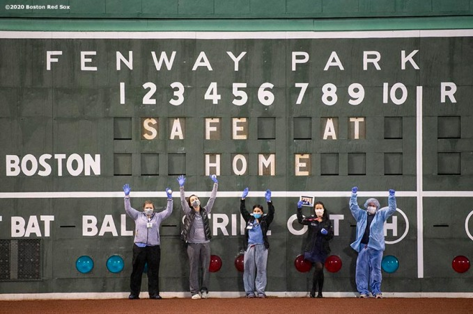 BOSTON, MA - APRIL 9: Medical professionals from Beth Israel Deaconess Medical Center pose for a photograph in front of the Green Monster scoreboard as they are welcomed onto the empty field at Fenway Park in recognition of their work during the coronavirus pandemic on April 9, 2020 at Fenway Park in Boston, Massachusetts. The welcoming was filmed for the 'Some Good News With John Krasinski' YouTube series. (Photo by Billie Weiss/Boston Red Sox/Getty Images) *** Local Caption ***
