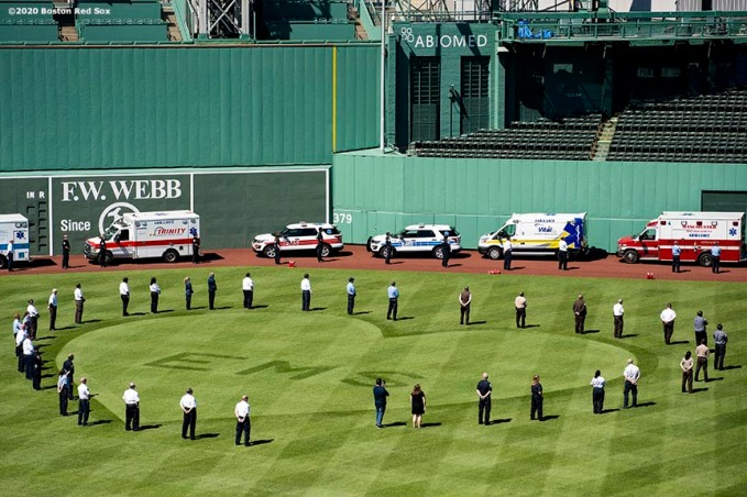 "BOSTON, MA - MAY 20: EMT's surround an outfield grass pattern during the ""Convoy of Champions"" honoring Massachusetts EMS professionals with a convoy of 50 ambulances that traveled from UMass Medical Center in Worcester to Fenway Park during the coronavirus pandemic on May 20, 2020 at Fenway Park in Boston, Massachusetts. (Photo by Billie Weiss/Boston Red Sox/Getty Images) *** Local Caption ***"