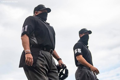 BOSTON, MA - AUGUST 19: Umpires wear masks as they walk onto the field before a game between the Boston Red Sox and the Philadelphia Phillies on August 19, 2020 at Fenway Park in Boston, Massachusetts. The 2020 season had been postponed since March due to the COVID-19 pandemic. (Photo by Billie Weiss/Boston Red Sox/Getty Images) *** Local Caption ***