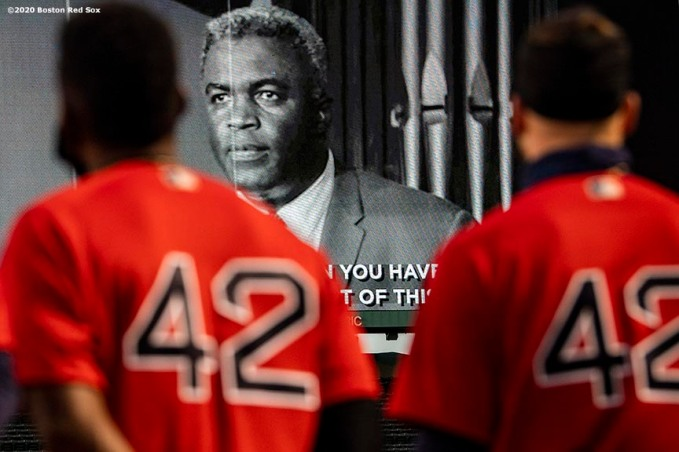 BOSTON, MA - AUGUST 28: Jackie Bradley Jr. #19 and Alex Verdugo #99, both wearing the number 42, look on as a video displays the image of Jackie Robinson during a pre-game ceremony in recognition of Jackie Robinson Day before a game between the Boston Red Sox and the Washington Nationals on August 28, 2020 at Fenway Park in Boston, Massachusetts. The 2020 season had been postponed since March due to the COVID-19 pandemic. (Photo by Billie Weiss/Boston Red Sox/Getty Images) *** Local Caption *** Jackie Bradley Jr.; Alex Verdugo