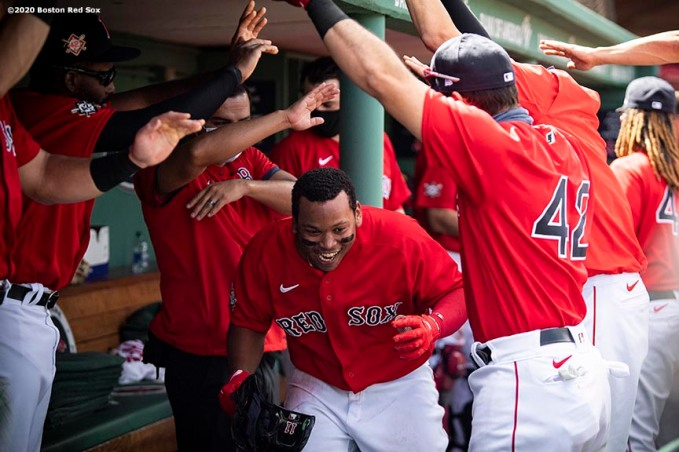 BOSTON, MA - AUGUST 30: Rafael Devers #11 of the Boston Red Sox reacts with teammates after hitting a two run home run during the third inning of a game against the Washington Nationals on August 30, 2020 at Fenway Park in Boston, Massachusetts. The 2020 season had been postponed since March due to the COVID-19 pandemic. (Photo by Billie Weiss/Boston Red Sox/Getty Images) *** Local Caption *** Rafael Devers